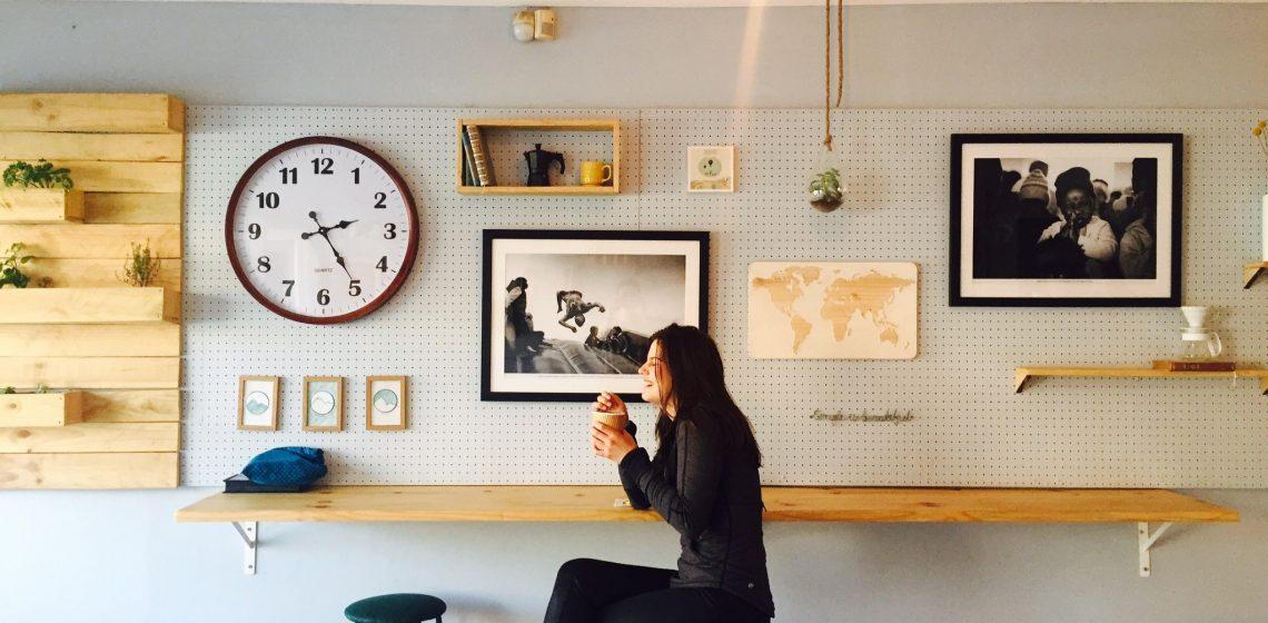 Frau trinkt Kaffee vor einer Wand mit Bildern
